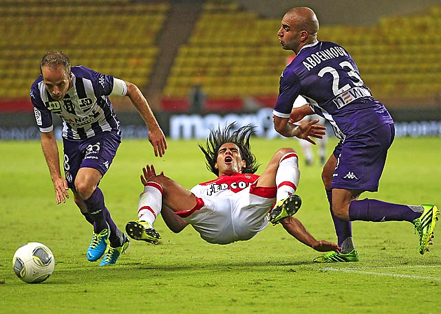 Monaco's Falcao, center, challenges for the ball with Toulouse's Etienne Didot of France, left, and Aymen Abdennour of Tunisia during their French League One match in Monaco stadium. The match was played at the empty stadium because of earlier fan trouble in May.