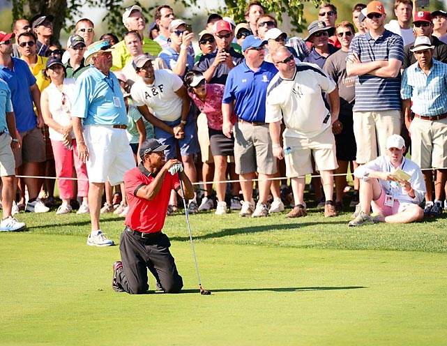 Tiger Woods drops to his knees on the 13th fairway during round four at the Barclays.