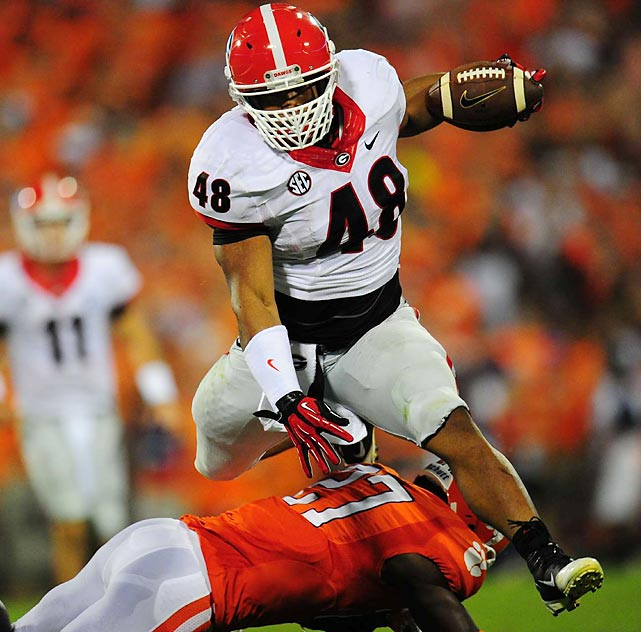 Georgia fullback Quayvon Hicks hurdles Clemson safety Robert Smith during the Tigers' 38-35 victory last Saturday. Hicks gained 38 yards on three carries, including a one-yard touchdown run in the second quarter -- one of five rushing TDs in the game for the Bulldogs.
