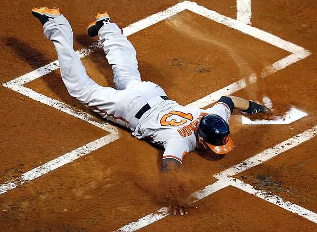 Orioles third baseman Manny Machado slides into home to score a first-inning run against the Red Sox on a double by first baseman Chris Davis on Aug. 28. Despite trailing Baltimore 3-1 in the seventh, Boston rallied for a 4-3 win, increasing their lead over the third-place Orioles in the American League East to 7½ games.