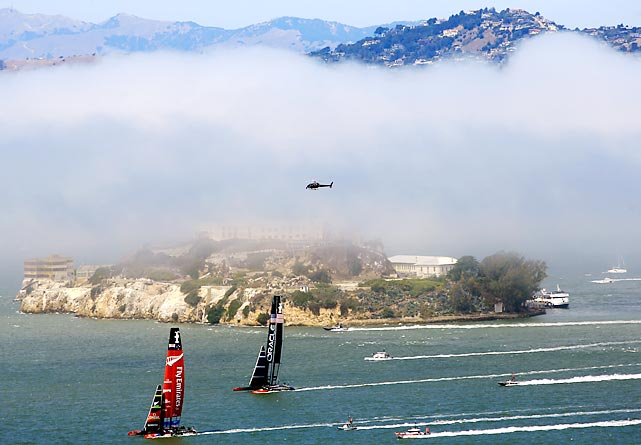 Emirates Team New Zealand (red sail) surges past Oracle Team USA (blue sail) to the windward side of foggy Alcatraz Island en route to victory in race 3 of the America's Cup finals on Sept. 8. Through Wednesday, the Kiwis held a 4-1 lead in the best-of-17 series.