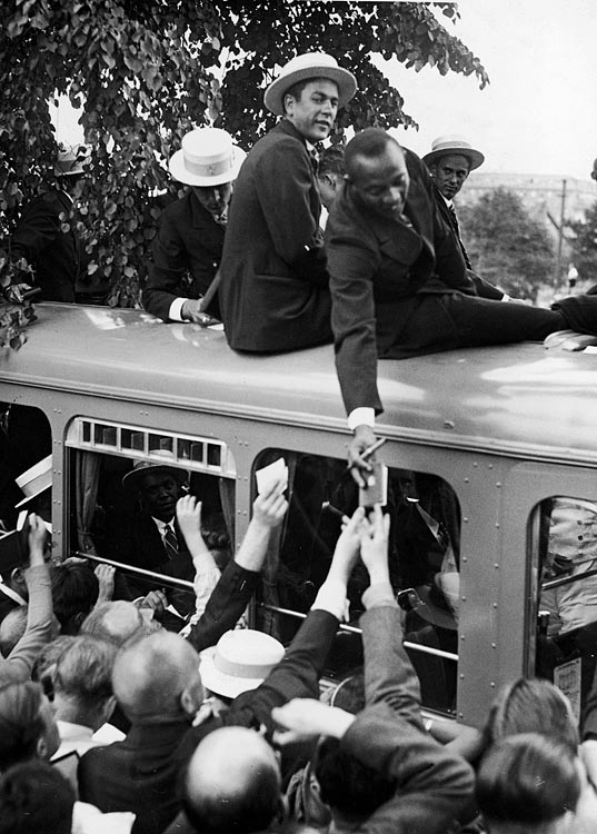 Owens signs autographs for German fans from atop the U.S. Olympic Team's bus during the opening ceremonies of the Olympic Games in Berlin in July 1936.