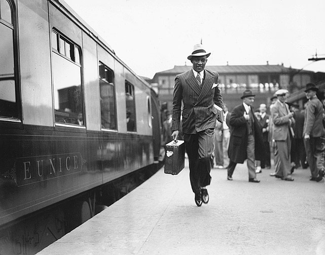 A snappily dressed Owens makes a dash for a train at London's Waterloo station. He was on his way to joining the liner 'Queen Mary' en route for New York.