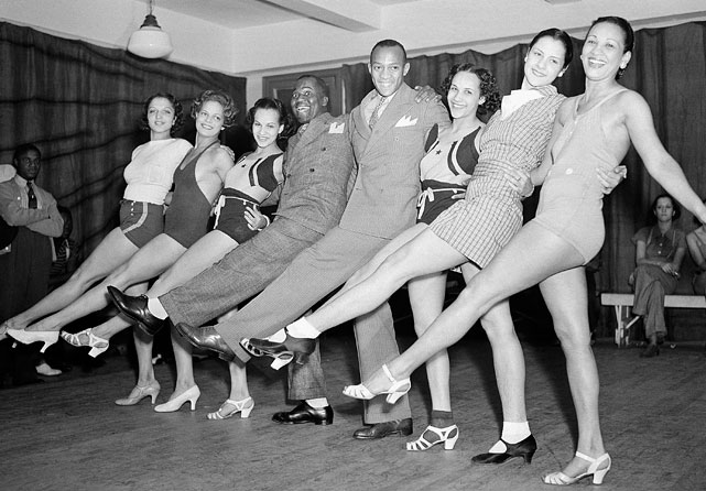 Owens, to the right of tap dancer Bill Robinson, poses with a bevy of dancers on Sept. 1, 1936, all rehearsing for the Cotton Club revue opening in New York.