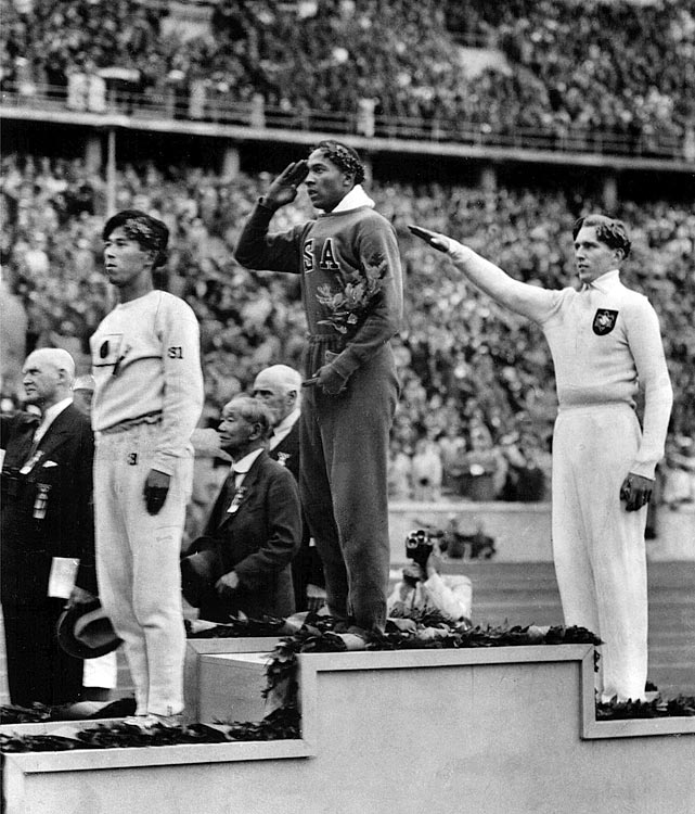 Owens salutes during the presentation of his gold medal for the long jump on Aug. 4, after defeating Nazi Germany's Lutz Long (right). Naoto Tajima of Japan (left) placed third.