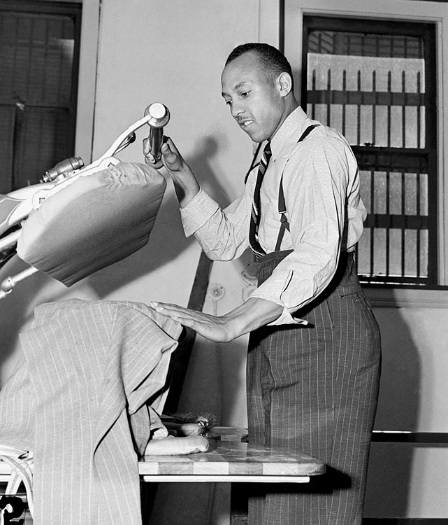 Owens opened a dry cleaning shop in Cleveland, and is shown working on the first suit to be brought in, Aug. 25, 1938.