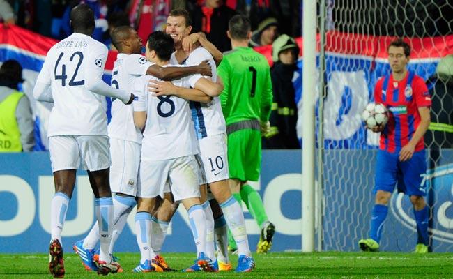 Edin Dzeko (10) celebrates after scoring Manchester City's opening goal.