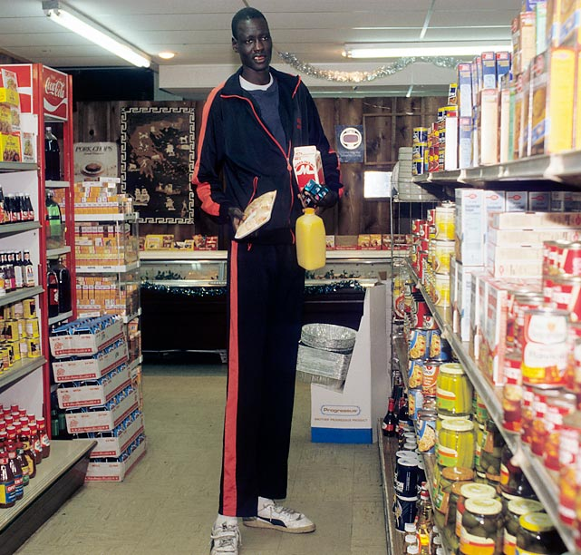 Leave it up to Manute Bol to make something as mundane as buying milk seem extraordinary. This photo was taken in 1984, when he was a student-athlete at the University of Bridgeport.