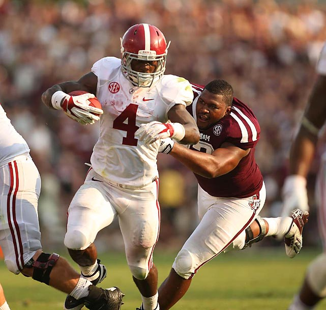 Alabama sophomore running back T.J. Yeldon fights through a tackle attempt by the helmet-less Alonzo Williams. Yeldon finished the day with 149 yards rushing and the Crimson Tide secured a 49-42 victory.