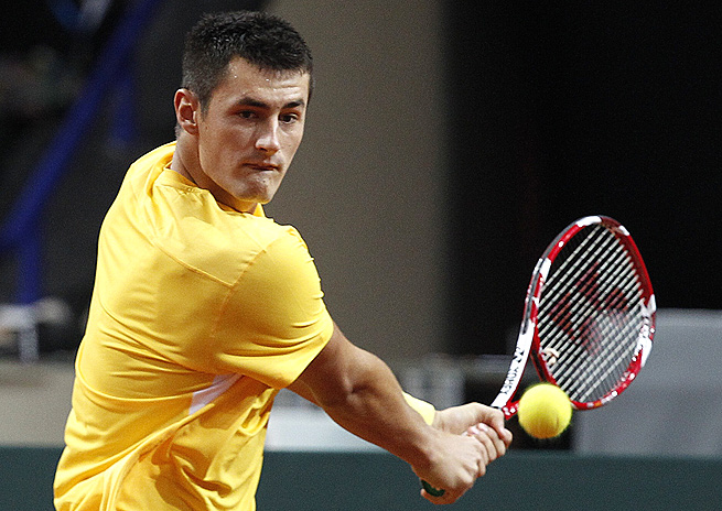 Bernard Tomic advanced to the second round in Bangkok when Ivo Karlovic retired with a back injury.