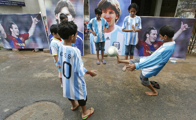 Children in Kolkata kick a soccer ball in Messi jerseys in front of images of the Argentinian star.