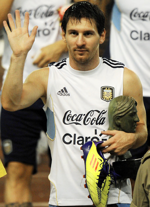 Lionel Messi gestures to the throng of Indian supporters following a training session in Kolkata.
