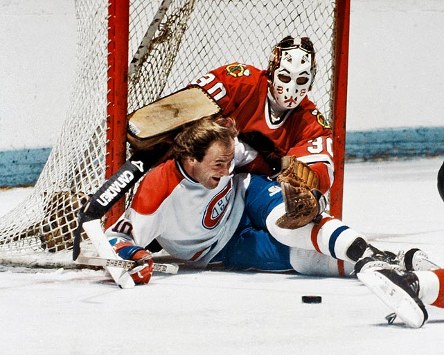 The Canadiens' Guy Lafleur slides into Blackhawks goalie Murray Bannerman while trying to control a loose puck near the net at the Montreal Forum in the early 1980s.