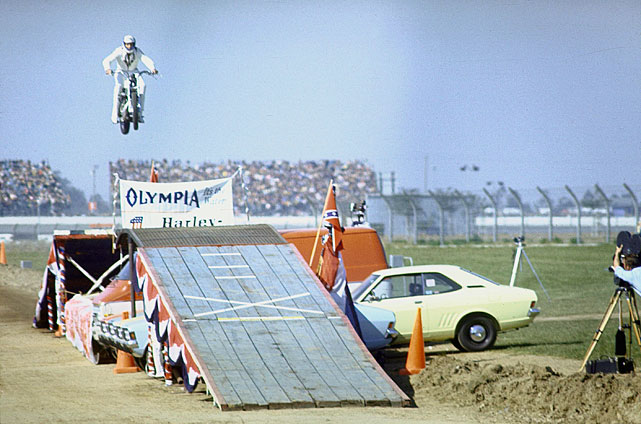 Daredevil motorcyclist Evel Knievel soars through the air while performing a stunt in March 1971.