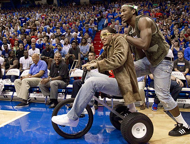 Kansas guard Niko Roberts (front) peddled a tricycle as Kansas guard Wayne Seldon, Jr., gave him a push, as they took the court for their skit during the University of Kansas Late Night.