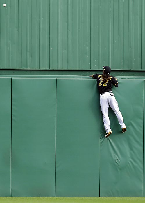 Pittsburgh Pirates center fielder Andrew McCutchen hangs on to the center field wall and watches a two-run home run by St. Louis Cardinals' Matt Holliday in the sixth inning of Game 4 of the NL Division Series.