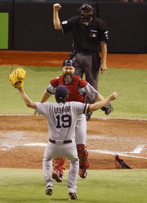 Boston Red Sox relief pitcher Koji Uehara celebrates with catcher Jarrod Saltalamacchia after eliminating the Tampa Bay Rays and advancing to the American League Championship Series.