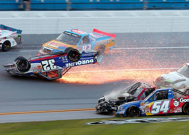 Miguel Paludo slides down the track on his roof as Darrell Wallace Jr., Jeb Burton and Kyle Busch crash on the last lap of the Camping World Truck Series race at Talladega Superspeedway.