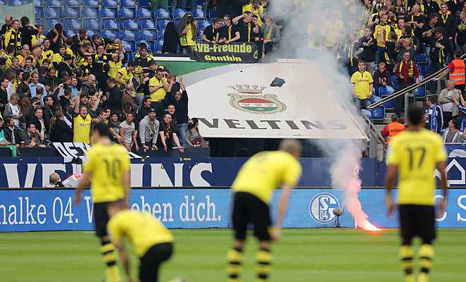 Dortmund fans delayed their team's game against Schalke after throwing flares on the field.