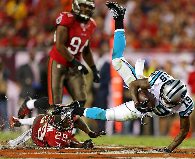 Carolina wide receiver Ted Ginn is tackled by Bucs defensive back Leonard Johnson. The Panthers won, 31-13, dropping the Buccaneers to 0-7.