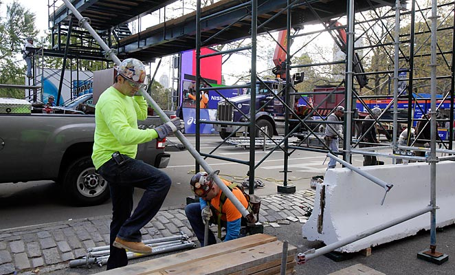 Workers install a photo bridge before the 2012 edition of the New York City marathon, which was canceled due to hurricane Sandy.