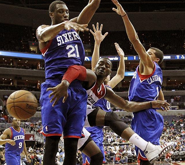 Washington Wizards point guard John Wall sneaks a pass around 76ers forward Thaddeus Young.
