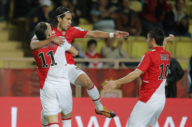 Monaco forward Radamel Falcao jumps into the arms of teammate Lucas Ocampos in celebration of his ninth Ligue 1 goal of the season in his side's 1-1 draw with Evian on Friday.