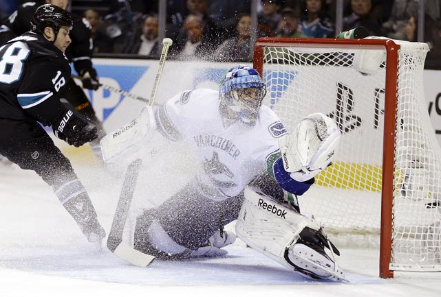 Sharks forward Mike Brown scores past Canucks goalie Roberto Luongo. Vancouver won 4-2, handing San Jose just its second regulation loss of the season.