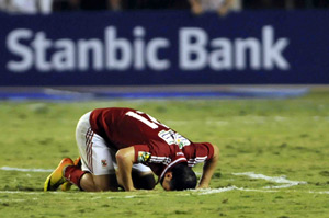 Al Ahly player Ahmed Abdul Zaher kneels after winning the African Champions League title.