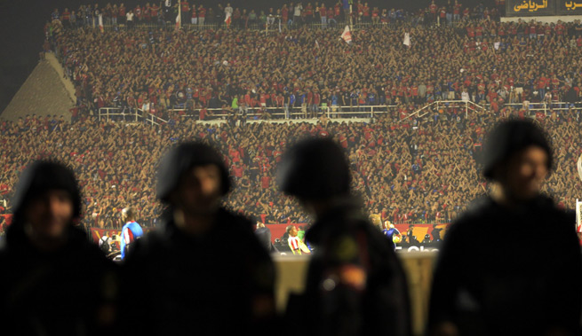 Riot police stand on guard as Egypt's Al Ahly fans cheer during their African Champions League final soccer match against South Africa's Orlando Pirates at the Arab Contractors Stadium in Cairo.