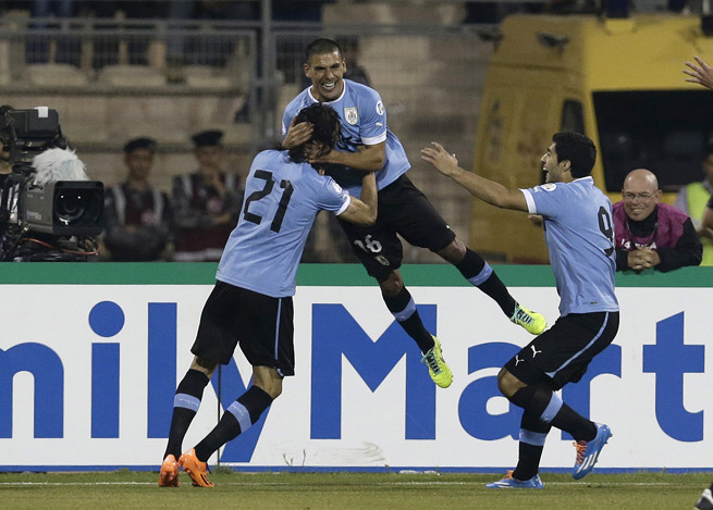 Maxi Pereira celebrates with Edinson Cavani (left) and Luis Suarez (right) after scoring the opening goal in Uruguay's 5-0 World Cup qualifying playoff victory over Jordan in Amman on Wednesday.