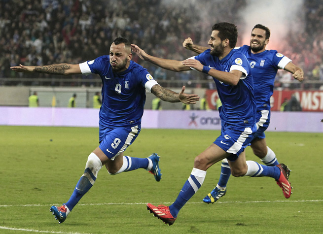 Greece's Kostas Mitroglou celebrates after his second, and his country's third, goal of the day as the Greeks lead Romania 3-1 heading into the second leg of their World Cup qualifying playoff.