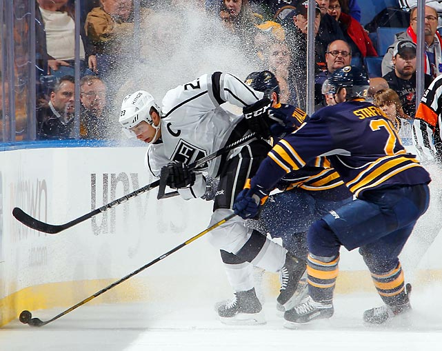 Dustin Brown of the Los Angeles Kings attempts to control the puck against Henrik Tallinder and Drew Stafford of the Buffalo Sabres. Buffalo won 3-2.