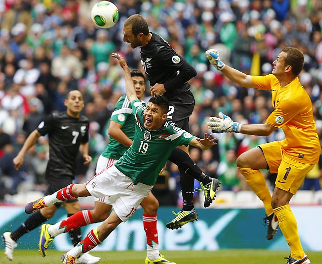 Mexico's Oribe Peralta, bottom, jumps for the ball with New Zealand's Jake Butler, top, and New Zealand's goalkeeper Glenn Moss, right, at a 2014 World Cup playoff first round soccer match in Mexico City.