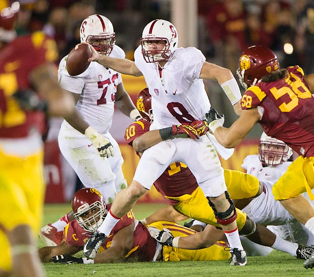 Stanford quarterback Kevin Hogan throws an interception as he's wrapped up by USC defenders.