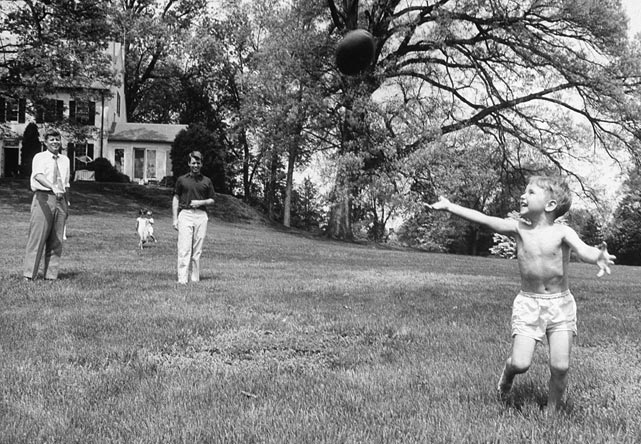 Senator John F. Kennedy throws a football to his nephew Bobby Jr. as his brother Robert looks on, in his yard at Hickory Hill, Va., in 1957.