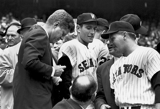 President John F. Kennedy signs baseballs for members of the Washington Senators prior to their opening day baseball game game against the Detroit Tigers on April 9, 1962 at Griffith Stadium in Washington, D.C.