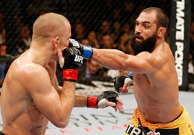 Georges St-Pierre (left) won a split-decision over Johny Hendricks, but took a beating in the process.