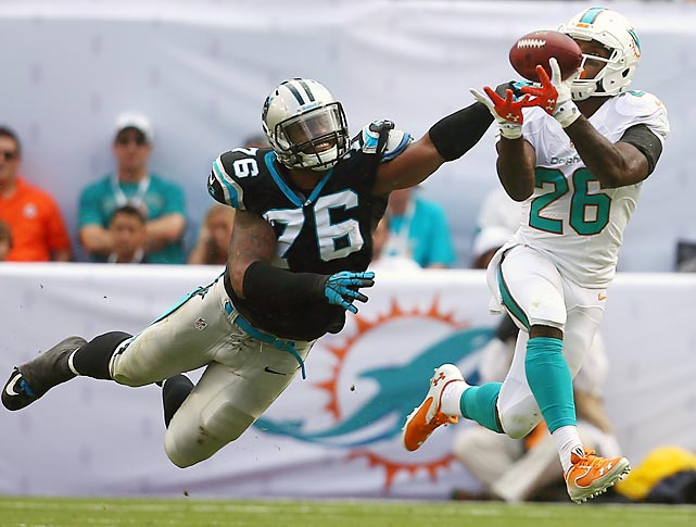 Dolphins running back Lamar Miller hauls in a pass just beyond the fingertips of Panthers defensive end Greg Hardy. Carolina staged a fourth-quarter comeback to move to 8-3.