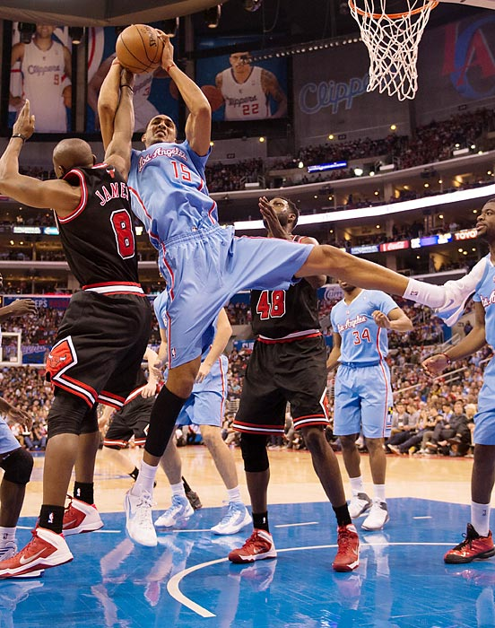 Clippers forward Ryan Hollins competes with Bulls guard Mike James for a rebound.