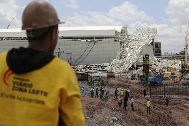 People stand near a metal structure that buckled on part of the Itaquerao Stadium in Sao Paulo, Brazil, which is set to host the World Cup opener in June. Two people died in the accident, according to authorities.