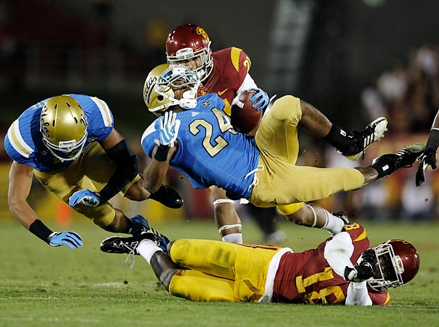 UCLA running back Paul Perkins falls to the turf at the Los Angeles Memorial Coliseum on a tackle by USC safety Dion Bailey. Perkins' fourth-quarter score put the finishing touch on 35-14 win for the Bruins, their second straight victory over the rival Trojans.