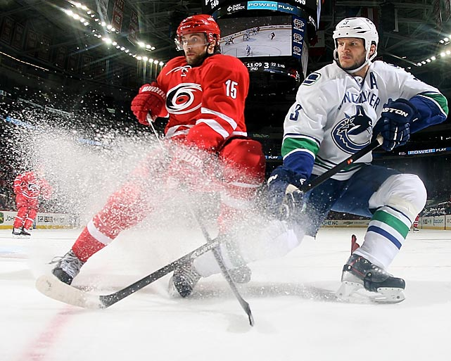 Vancouver Canucks defenseman Kevin Bieksa sprays ice as he battles for the puck with Carolina Hurricanes left winger Tuomo Ruutu during a game Sunday in Raleigh, North Carolina. Bieksa's Canucks got the best of Ruutu's Hurricanes, earning 3-2 win on the road.