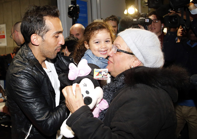 Zahit Belounis, holding his daughter Maissa, smiles as he meets his mother Faouzia after arriving in France from Qatar. He had been refused his exit visa because of a legal dispute over unpaid wages with Qatari club Al-Jaish.