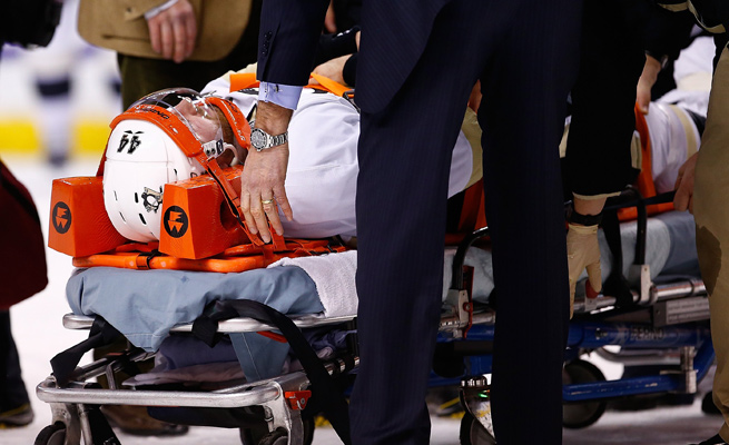 Brooks Orpik was taken off the ice on a stretcher after an altercation in the first period of Saturday's game in Boston.