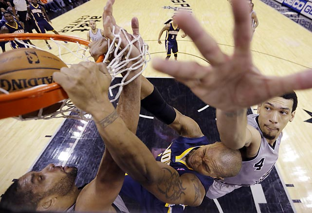 Indiana Pacers power forward David West slams in a dunk around the outstretched arms of Tim Duncan and Danny Green of the San Antonio Spurs during the second half of the teams' Saturday game. West finished with 20 points as the NBA-leading Pacers defeated the Spurs 111-100.