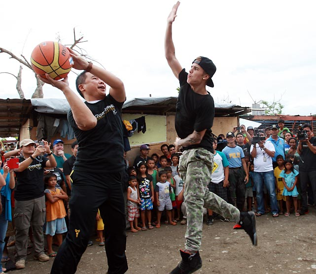 Nothing like a little biebsketball to make life brighter in the wake of a Super Typhoon. Here we have the beloved entertainer showin' 'em how the D is done at San Jose Elementary School in Tacloban, Leyte, Philippines. The Biebs was on a campaign to help raise money for the storm's victims and, in the process, he raised his game as well as his hand, as you can see.