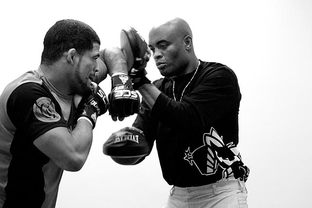 Anderson Silva warms up Paulo Bananada back-stage at a regional MMA event.