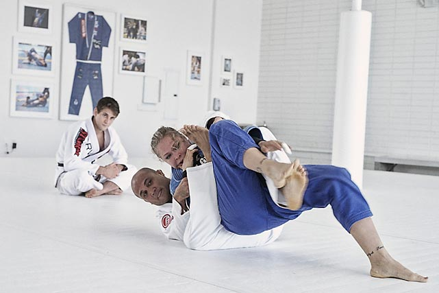 Ronda Rousey rolling with BJ Penn as world jiu jitsu champion Rafael Mendes watches.