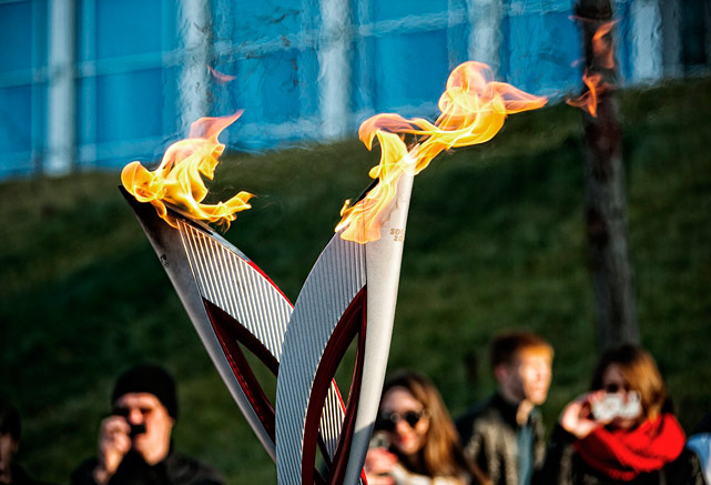 An Olympic torchbearer accidentally set his jacket on fire as he carried the flame through the Siberian town of Abakan.